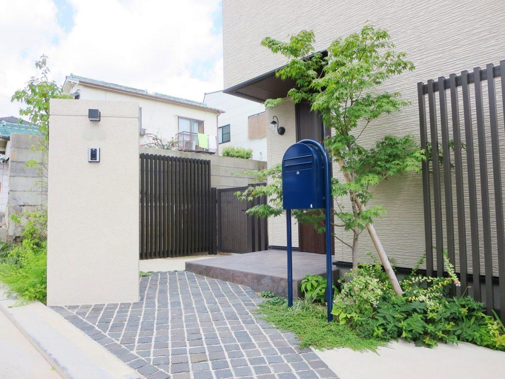 道路から斜めに入るデザインの白い門柱、黒いピンころ石の外構