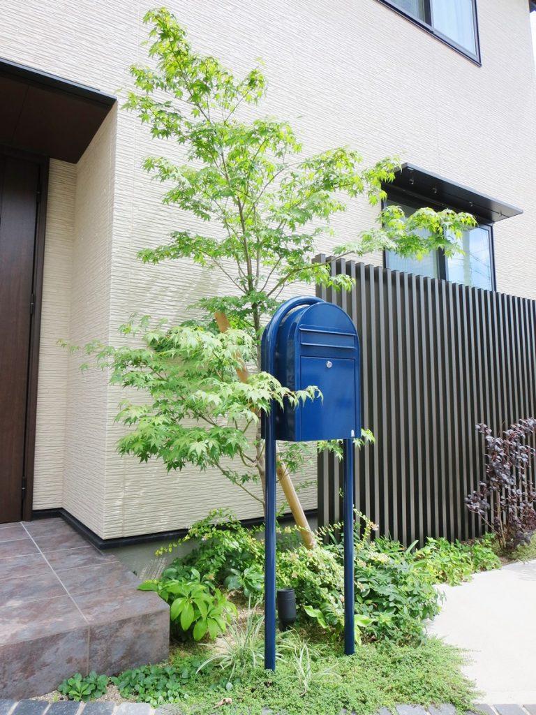 青いポストとモミジの気が中心にあるオープン外構