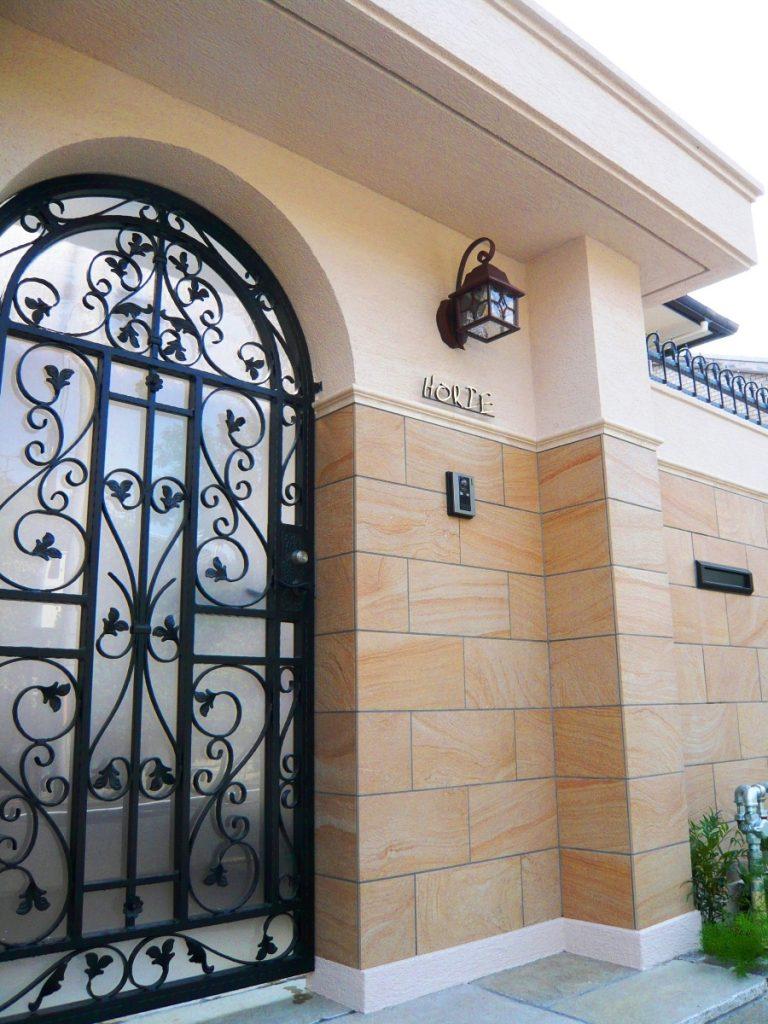 砂岩調石が貼られたゲートとアイアン門扉