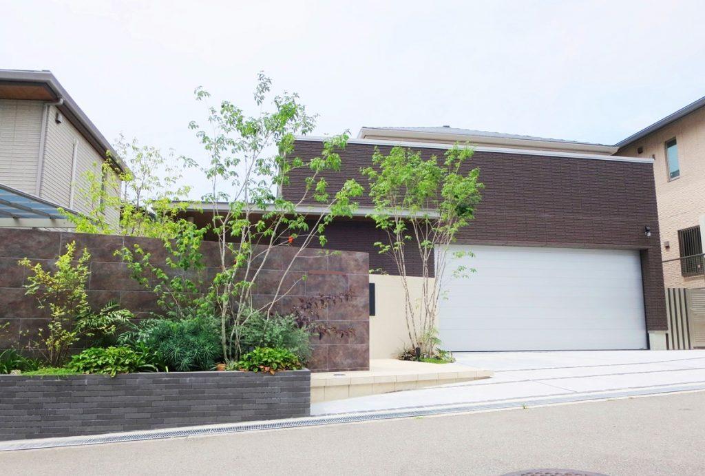 左手に茶色のタイルの門ペイがあるガレージの大きなお家