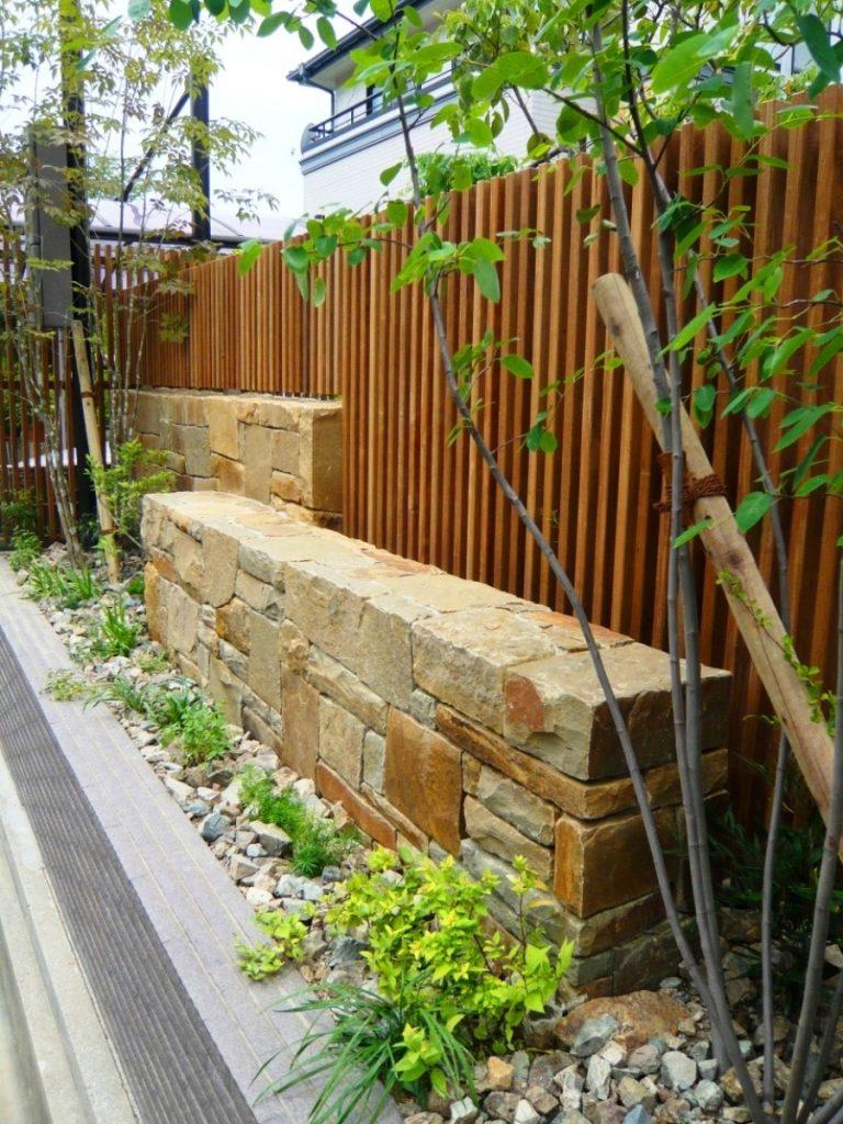 石張りのベンチの後ろに縦格子の塀と緑が多い外回り