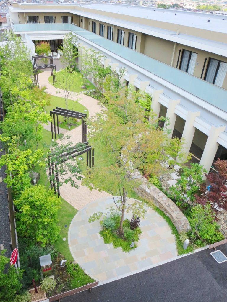 2階建ての建物の緑あふれる中庭を屋上から見た風景