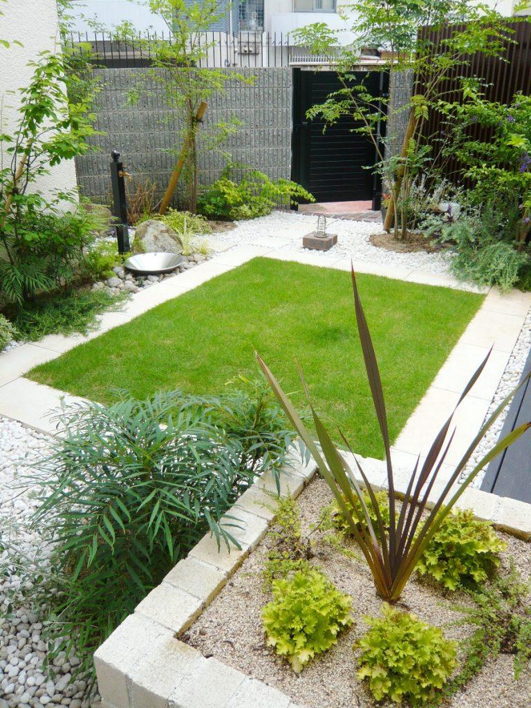 奥にはタイルに囲まれた芝の庭、手前にはホワイトレンガのフラワーボックス