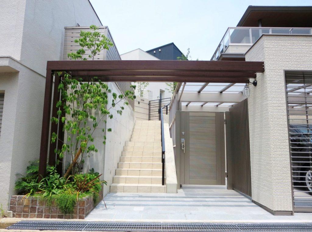 パーゴラ風ゲートのある外構、奥に階段が見える