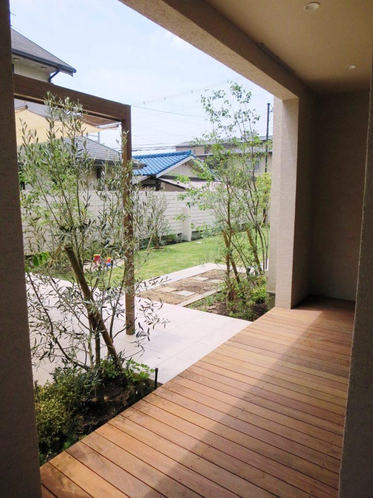 手前にウッドデッキ、左手にパーゴラ中央にオリーブの木がある庭の写真