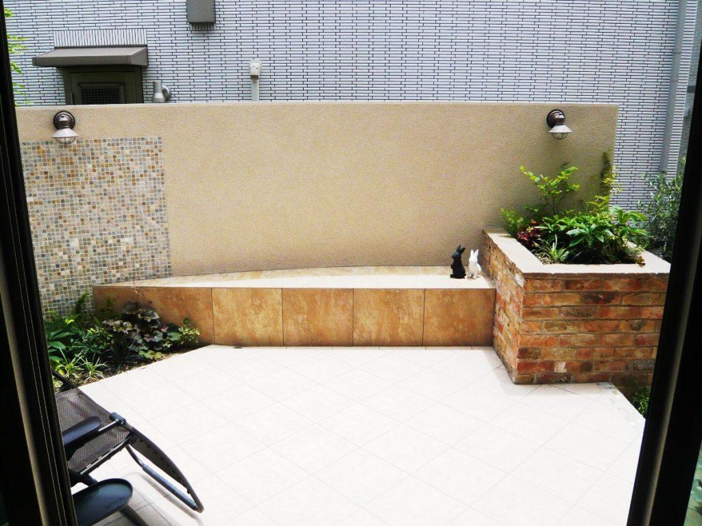 アールの壁とベンチのあるタイルテラス