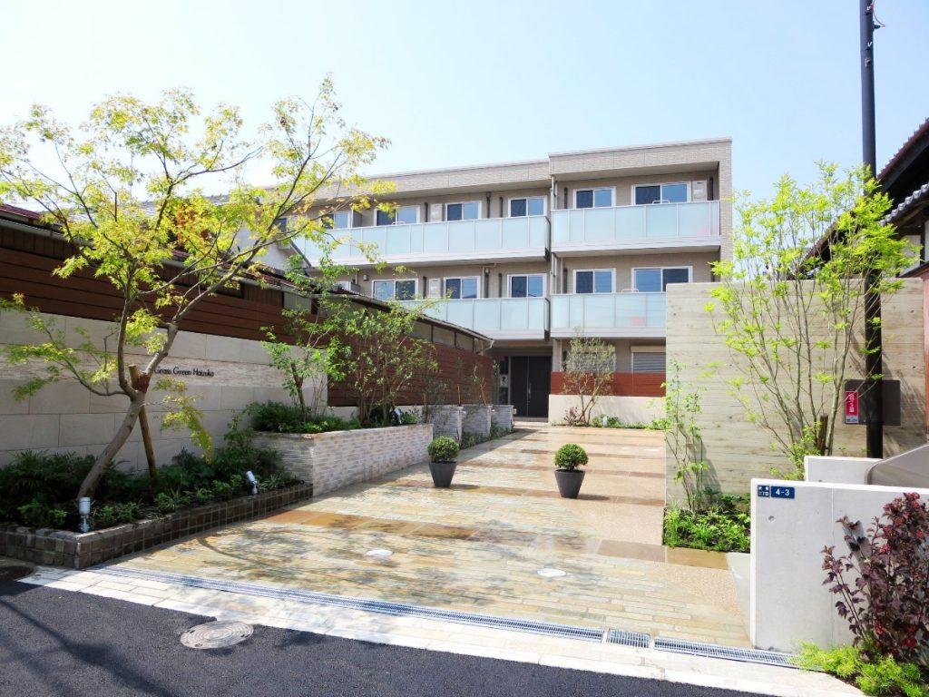 奥に3階縦のマンションが見え、左手はマンションの門壁、右には駐輪所の塀