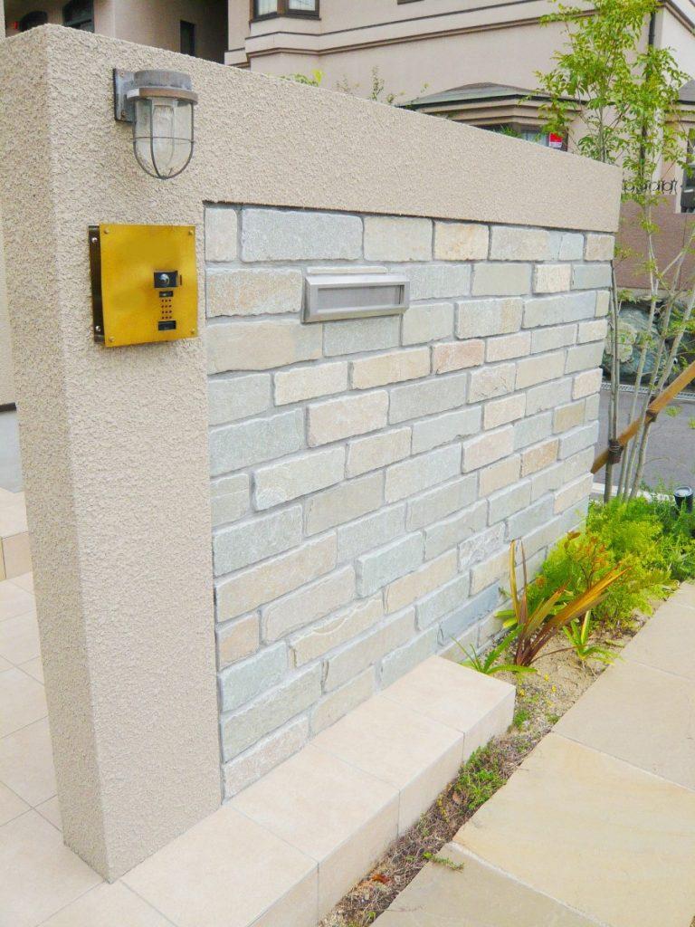 家の色に合わせた石張りの門壁