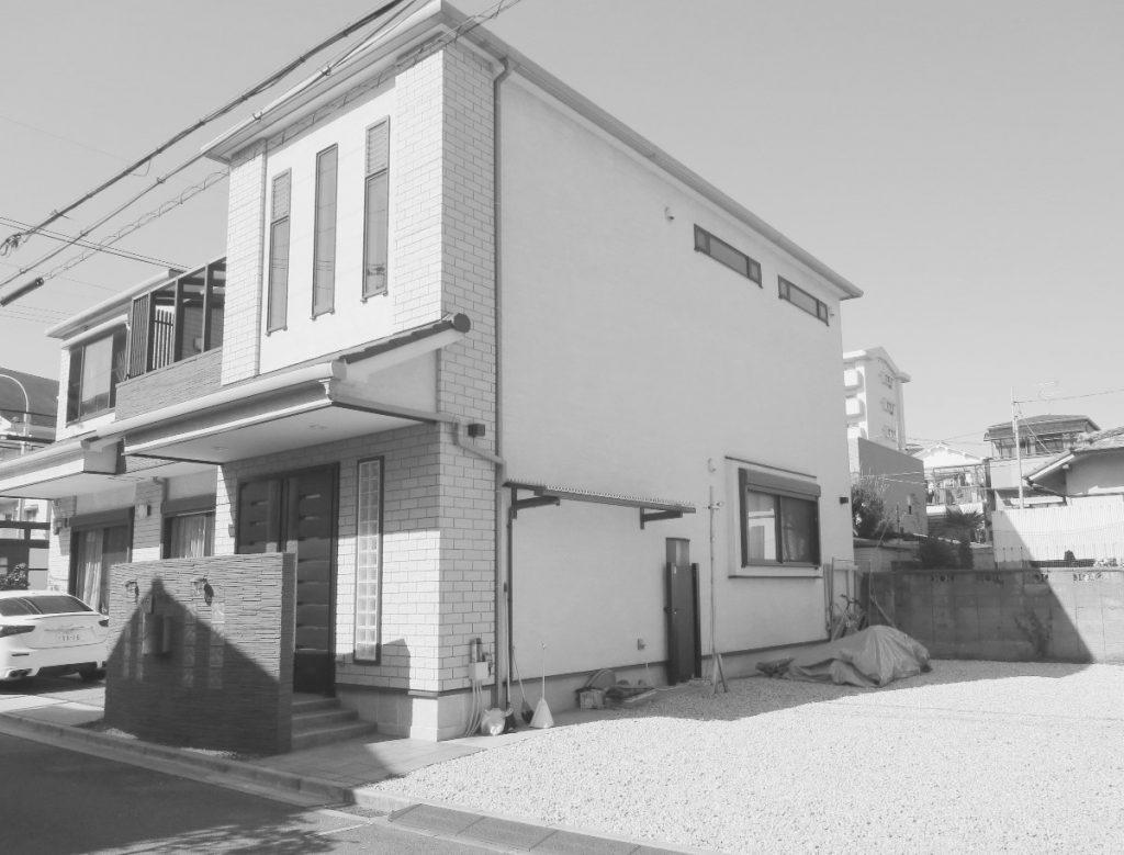 オープン外構の2階建ての家と左隣の空き地の写真