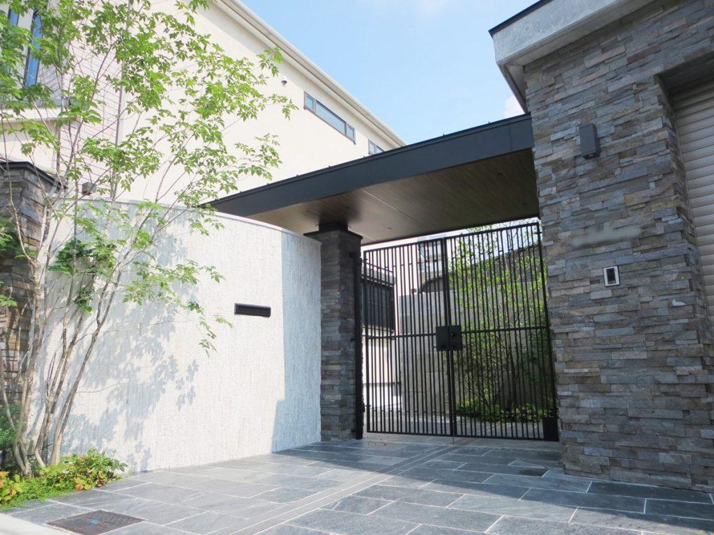 左手にアールの白い塀とアイアンの門扉右に石張りの門柱