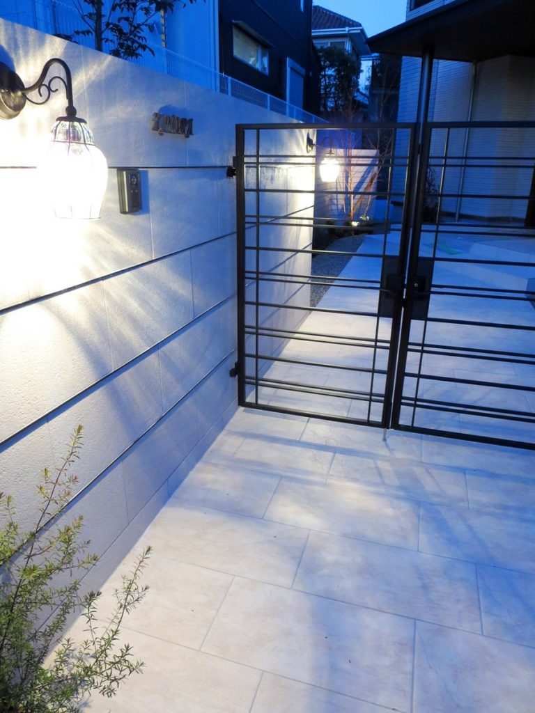左に白い壁、正面にアイアン門扉の夜景写真
