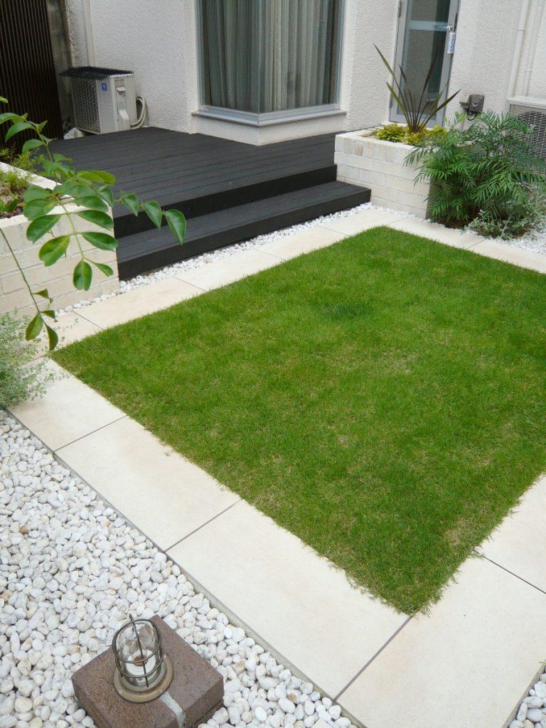左手奥にブラックのウッドデッキ、手前にはタイルで囲われた芝の庭