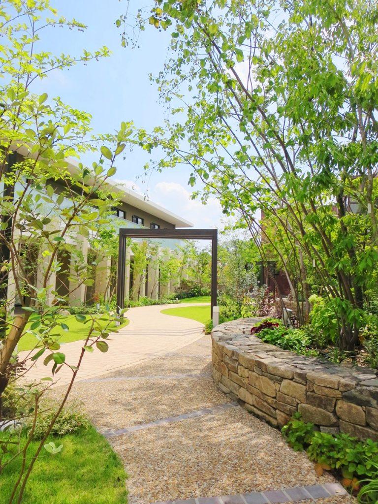 右手に石張りの花壇があり、そこには大きな樹木が植えられ、遠くには格子のゲートが見える