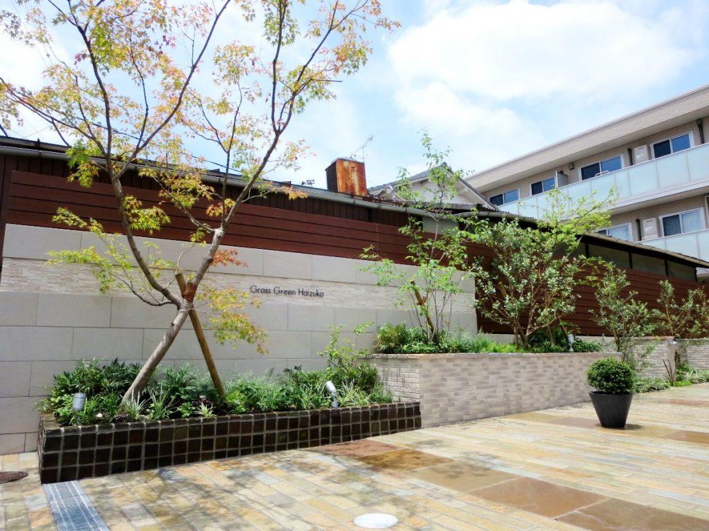 上の写真のプレハブの前に設けられたマンションのデザイン壁とシンボルツリー