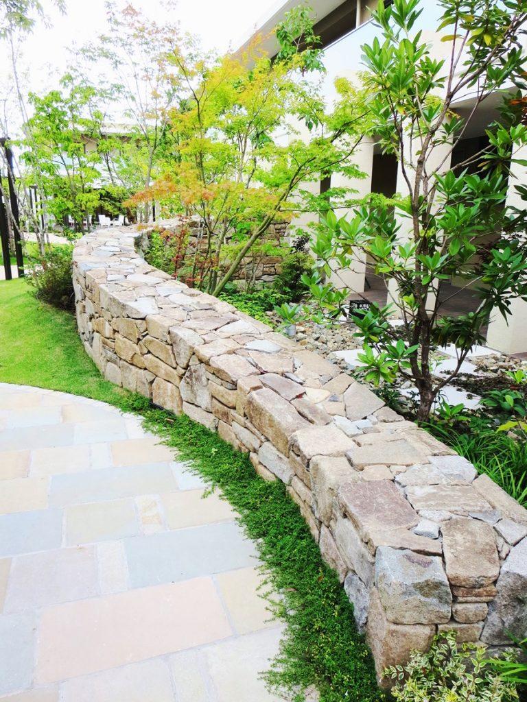 幅広の石張りの土留め、内側に植えられている樹木が右手にある