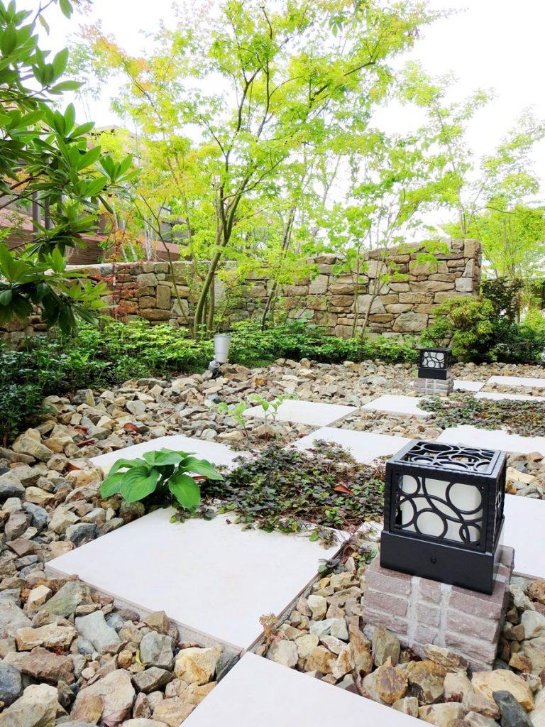 格子状に敷かれた方形の石板とごろた。奥には石張りの塀が見える